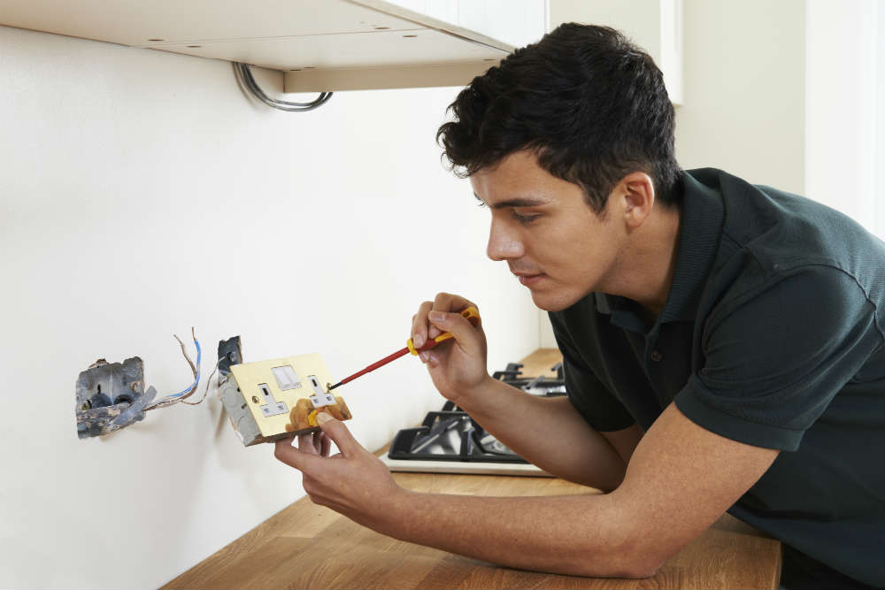 electrician fixing plug socket in student house