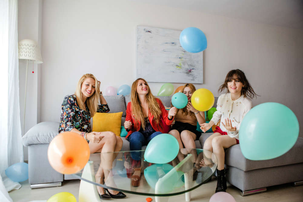 Girls on sofa surrounded by blue, orange and yellow balloons