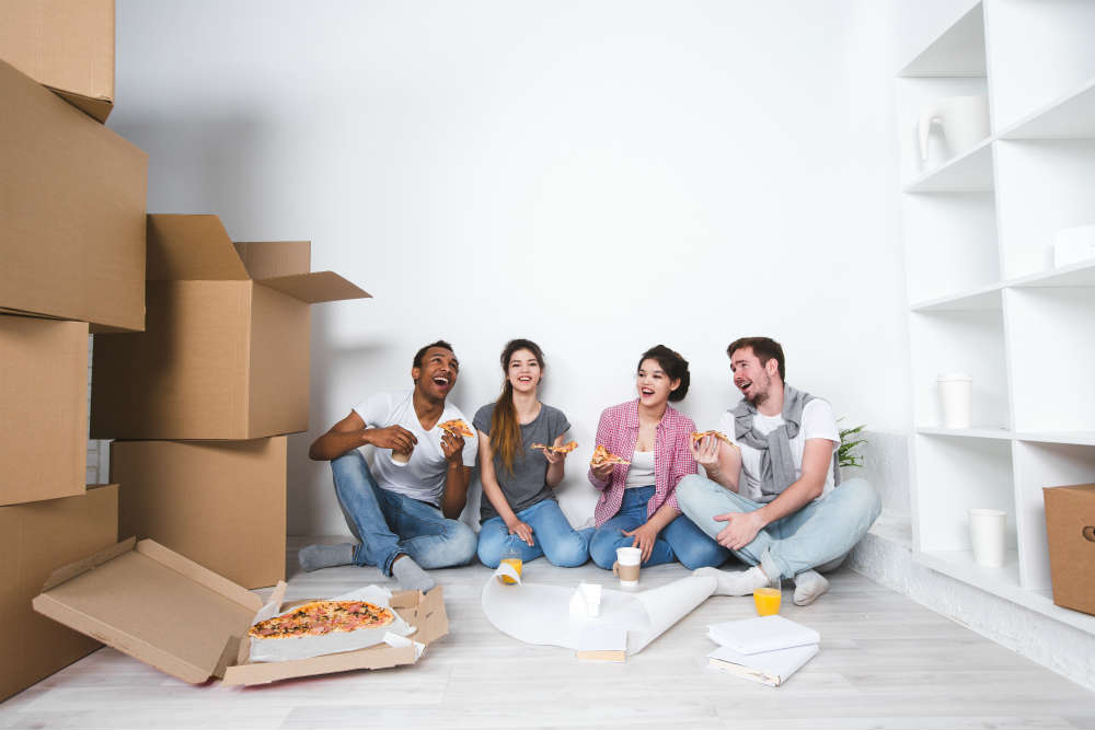 four friends sat on floor eating pizza after unpacking boxes in new house