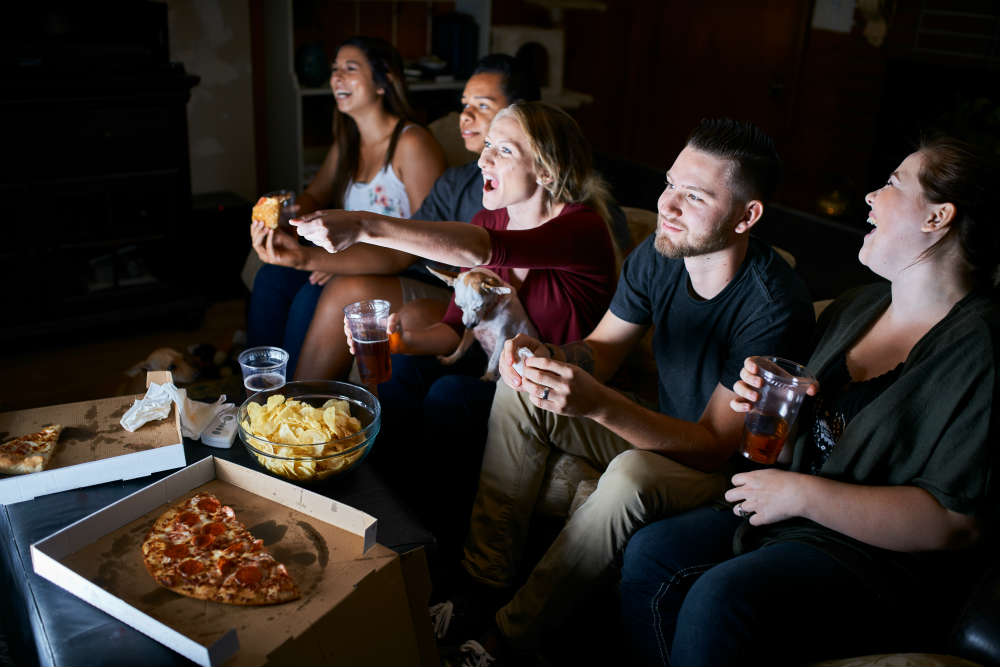 Students watching movie while eating pizza and crisps