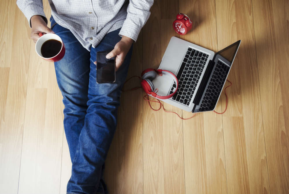 birdseye view of student sat with laptop and coffee on wooden floor